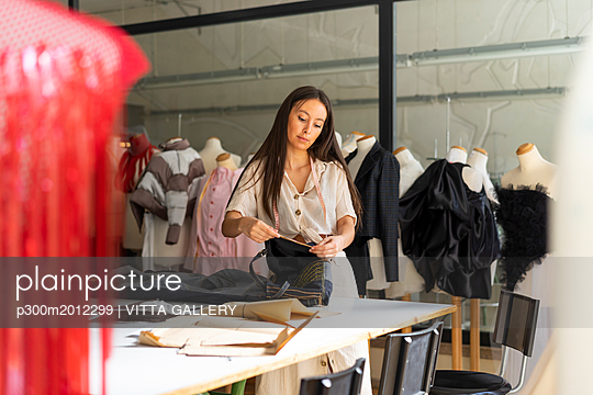Young fashion designer working in her studio - p300m2012299 von VITTA GALLERY