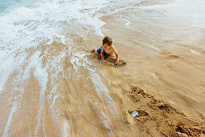 High angle view of shirtless boy playing on shore at beach - p1166m1543258 by Cavan Social