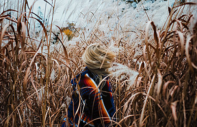 Playful woman tossing hair while standing amidst plants on field at Algonquin Provincial Park - p1166m1577895 by Cavan Images