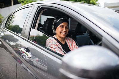 Asian woman driving car - p1166m2131285 by Cavan Images