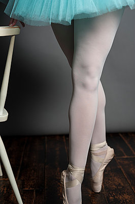 Female ballet dancer en pointe, steadying herself on the back of a white chair. - p1433m1531937 by Wolf Kettler