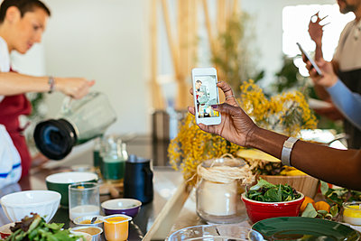 Close-up of woman taking smartphone picture of instructor working in a cooking workshop - p300m1587685 von Bonninstudio