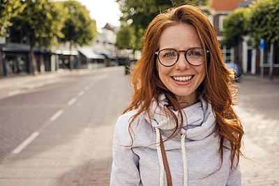 Redheaded woman with headphones in the city - p300m2023692 von Kniel Synnatzschke