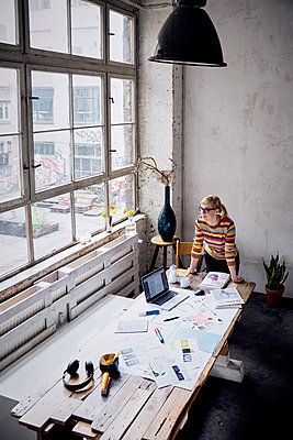 Woman standing at desk in a loft looking through window - p300m2030201 by Rainer Berg