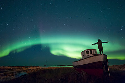 Norway, Lofoten Islands, Eggum, man admiring northern lights, standing on fishing boat - p300m2104634 by Valentin Weinhäupl