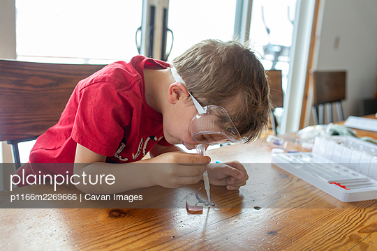 Boy leaning over chemistry set he is playing with - p1166m2269666 by Cavan Images