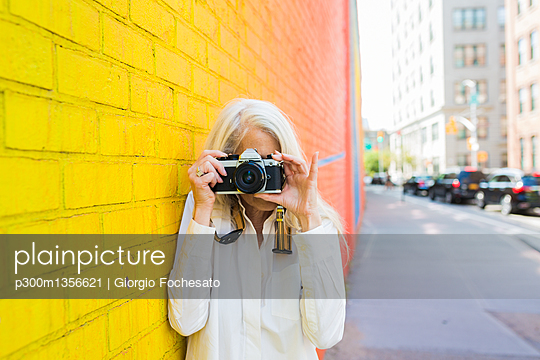 Mature woman leaning against wall taking picture with camera - p300m1356621 by Giorgio Fochesato