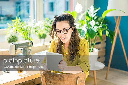 Portrait of smiling fashion designer sitting in her studio using tablet - p300m1581132 von Robijn Page