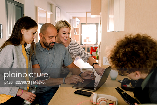 Woman discussing with man over laptop by daughter at kitchen island - p426m2279673 by Maskot