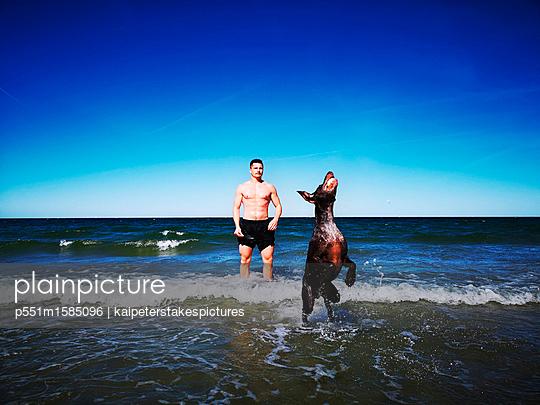 Mann und Hund spielen am Meer - p551m1585096 von Kai Peters