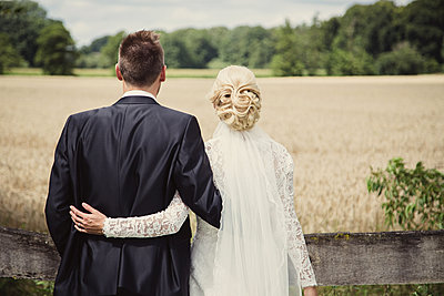 Bride and groom looking into the distance - p1351m2082321 by Janine Meyer