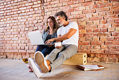 Businessman and woman sitting in a loft, using laptop, founding a start-up company - p300m1535092 by HalfPoint