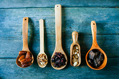 Row of different wooden spoons with dates, walnuts, currants, almonds and dark chocolate - p300m1535519 by Kiko Jimenez