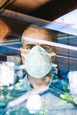 Mature man with protective mask looking through of the window, looking at camera - p300m2180471 by 27exp