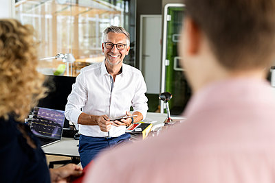 Smiling male business professional holding digital tablet while discussing with colleagues in office - p300m2267867 by Peter Scholl
