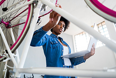 Young woman with laptop repairing bicycle at home - p300m2274822 by Giorgio Fochesato