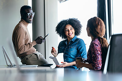 Smiling business people discussing while taking break at desk - p300m2275571 by Josep Suria