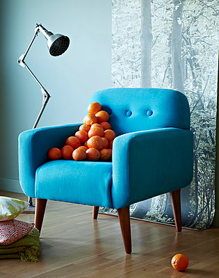 Stack of oranges on blue armchair with anglepoise lamp - p349m896309 by Jon Day