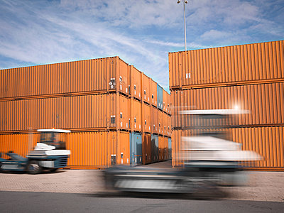 Trucks and shipping containers in port - p429m954633f by Monty Rakusen