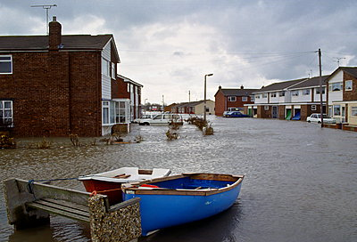Boats tethered to a stone bench in the flooded town of Towyn in North Wales - p871m884426 by Tim Graham
