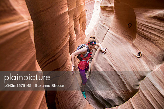 Woman canyoneering through narrow Zebra Canyon, Grand Staircase-Escalante National Monument, Utah, USA - p343m1578148 by Suzanne Stroeer