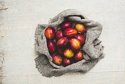 High angle close up of fresh damsons on grey cloth. - p1100m2084902 by Mint Images