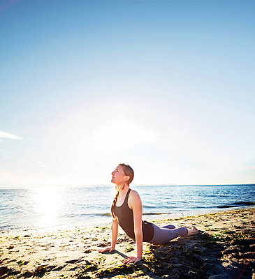 Woman practicing cobra pose at beach against sky during sunny day - p1166m1227818 by Cavan Images