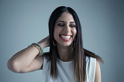 Portrait brunette Indian woman wearing bindi laughing with eyes closed - p1192m1213118 by Hero Images