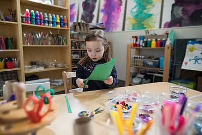 Preschool girl cutting construction paper for art and craft project in classroom - p1192m1560109 by Hero Images