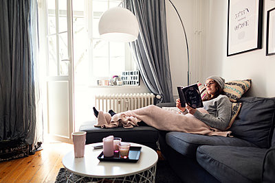 Lesend auf der Couch in einem gemütlichen Wohnzimmer - p1515m2182096 von Daniel K.B. Schmidt