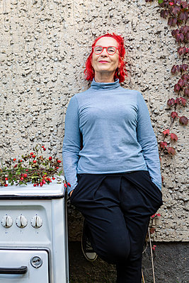 Portrait of smiling senior woman with red dyed hair leaning against house front - p300m2081282 by Julia Otto