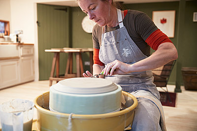 Woman working with a pottery wheel in her workshop - p300m2144633 by Pete Muller