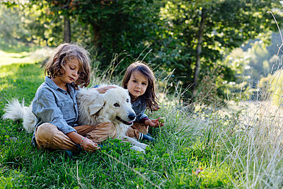 Two kids relaxing with dog on a meadow - p300m2144762 by Sofie Delauw