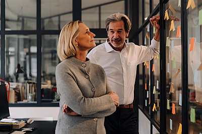 Businessman and businesswoman working on sticky notes at glass pane in office - p300m2156041 by Gustafsson