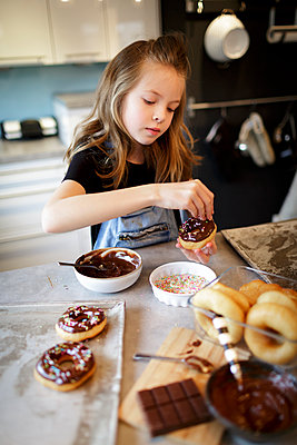 pretty girl bakes donuts with chocolate and sprinkles in modern kitchen, lower austria - p300m2180232 von Epiximages