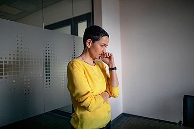Businesswoman thinking while standing in office - p300m2276094 by Oxana Guryanova