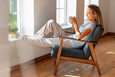 Happy woman holding coffee mug while sitting at window in living room - p300m2277511 by Steve Brookland