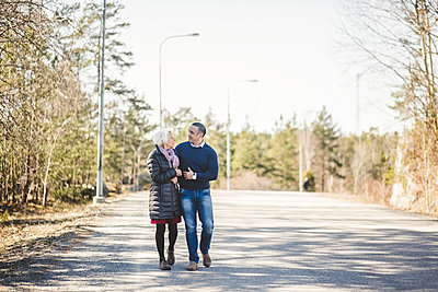 Full length of mature man walking arm in arm with mother on road - p426m2018548 by Maskot