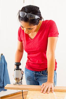 Mixed race woman using jigsaw - p555m1419266 by Jason Homa
