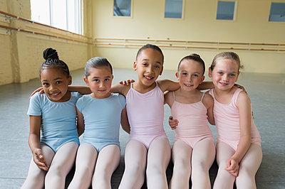 Portrait of smiling girls hugging on floor of ballet studio - p555m1491102 by Mark Edward Atkinson