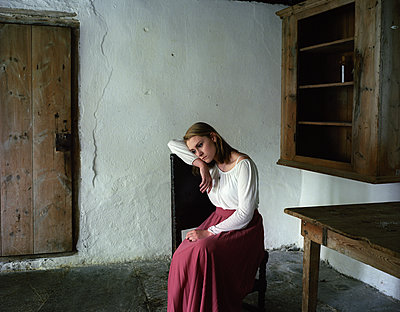 Sad young woman sits on chair - p945m1487985 by aurelia frey