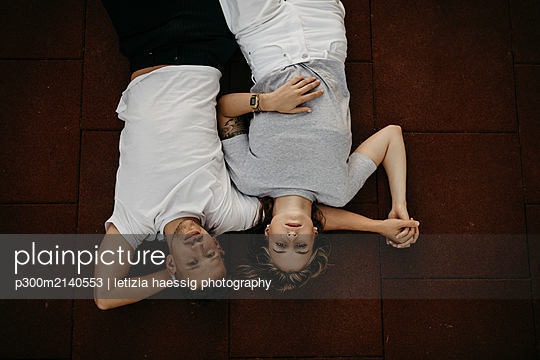 Young couple lying on the ground, from above - p300m2140553 by letizia haessig photography