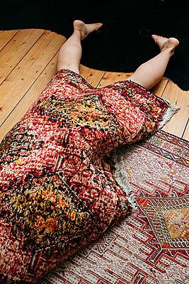 Woman rolled up in carpet - p1621m2254259 by Anke Doerschlen