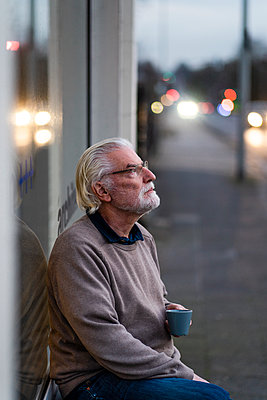 Thoughtful senior man sitting outside cafe at street - p300m2276862 by Robijn Page