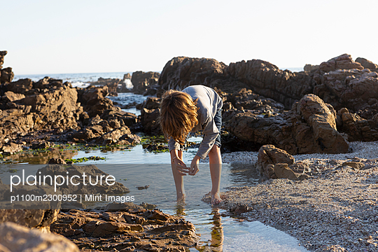 Young boy exploring a rock pool on the coast at sunset - p1100m2300952 by Mint Images