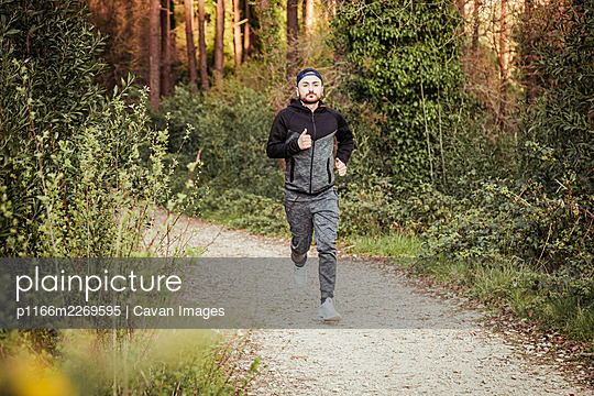 Man in cap and dark tracksuit running through the forest - p1166m2269595 by Cavan Images