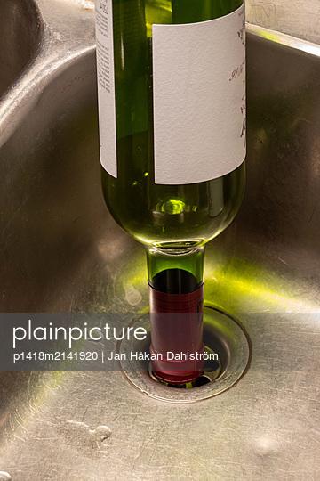 Wine bottle upside down in sink - p1418m2141920 by Jan Håkan Dahlström