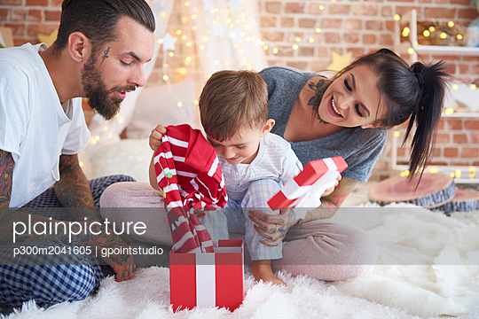 Boy opening Christmas present with his parents in bed - p300m2041605 by gpointstudio