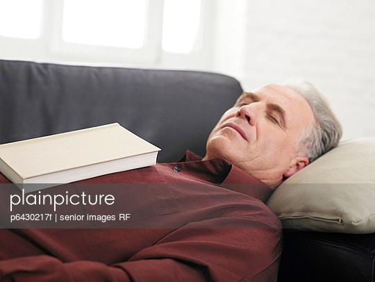 Aelterer Mann schlaeft auf dem Sofa  - p6430217f von senior images RF