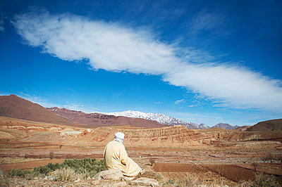 Morocco, Man with turban looking at the Atlas Mountains - p1167m2269954 by Maria Schiffer
